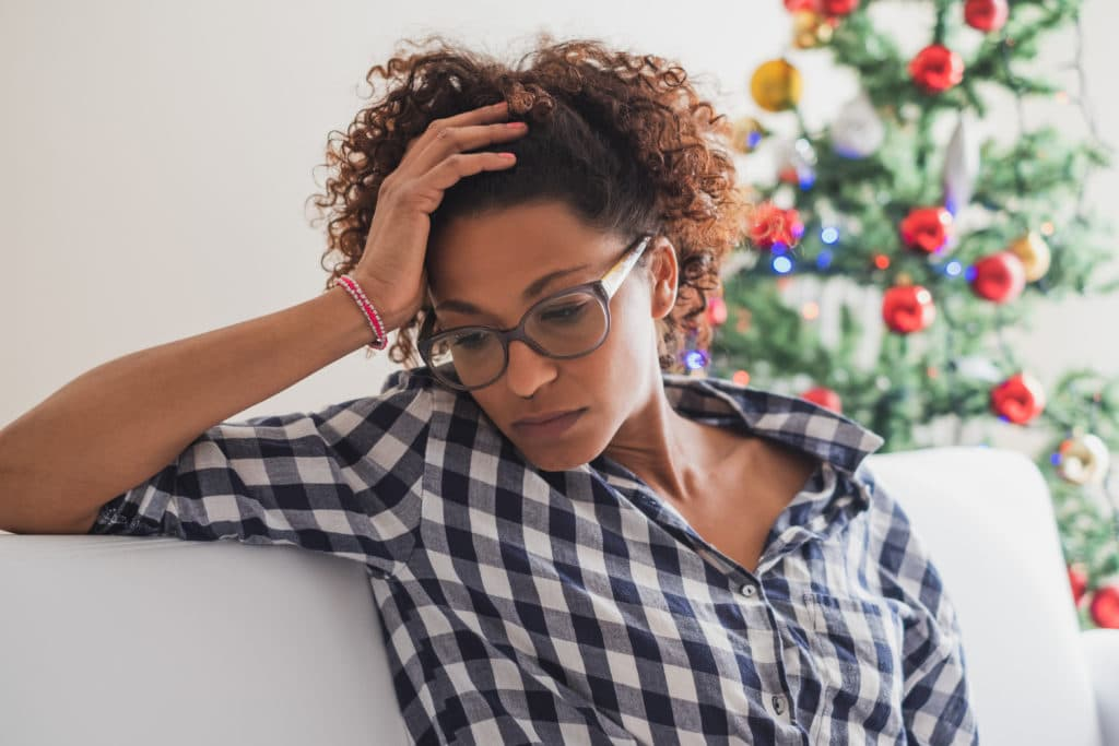 woman looking distressed with holiday tree in background